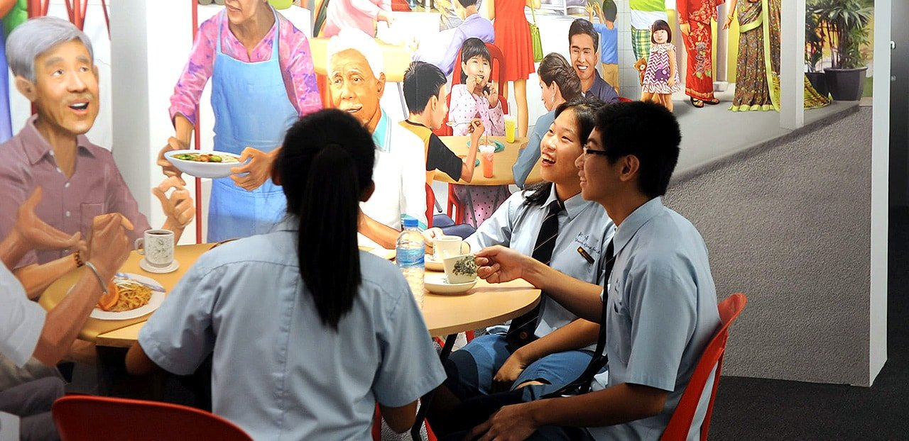 Students at a trick-eye wall mural depicting a coffee shop scene in Singapore